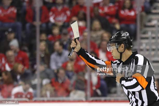 Referee Jean Hebert signals a penalty while holding a broken hockey stick as the Washington Capitals play against the Winnipeg Jets during the first...