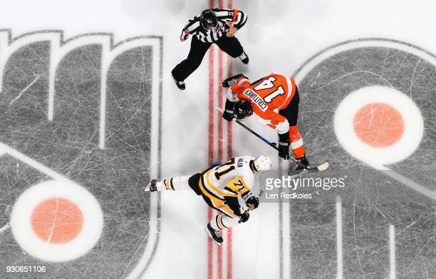Referee Jean Hebert watches Sean Couturier of the Philadelphia Flyers control the puck on a faceoff against Evgeni Malkin of the Pittsburgh Penguins...