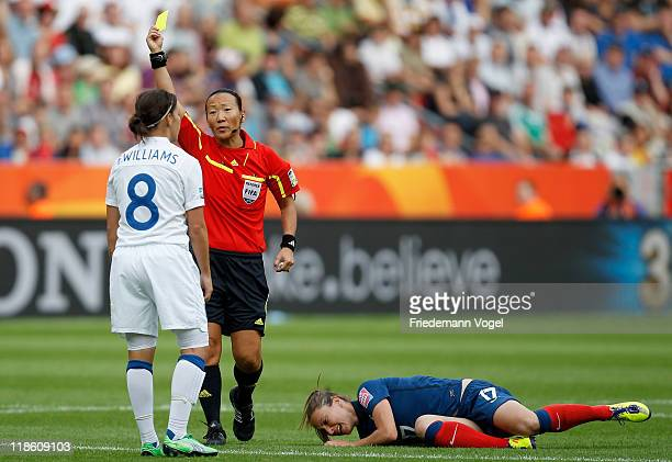 Referee Jenny Palmqvist of Sweden shows Fara Williams of England the yellow card after a foul on Gaetane Thiney of France during the FIFA Women's...