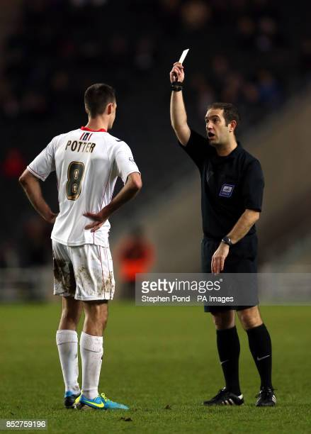 Referee Jeremy Simpson shows a yellow card to Milton Keynes Dons' Darren Potter