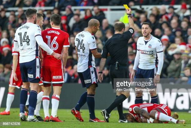 MIDDLESBROUGH ENGLAND DECEMBER Referee Jeremy Simpson shows Bolton Wanderers' Andrew Taylor a yellow card for a challenge on Middlesbrough's Britt...