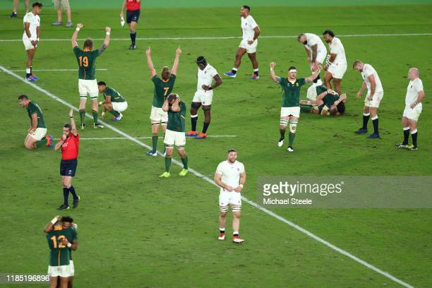 Referee Jerome Garces of France blows the full time whistle as players of South Africa show their jubilation at their side's 3212 victory over...