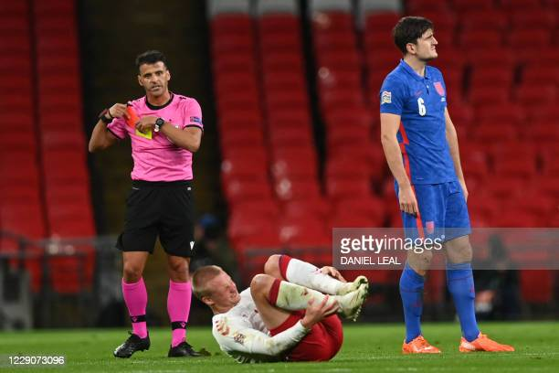 Referee Jesús Gil Manzano pulls out the red card for England's defender Harry Maguire's tackle on Denmark's striker Kasper Dolberg during the UEFA...