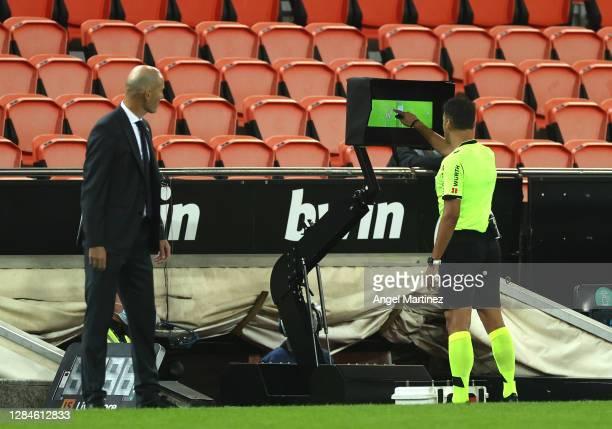 Referee Jesus Gil Manzano looks at the VAR monitor during the La Liga Santander match between Valencia CF and Real Madrid at Estadio Mestalla on...