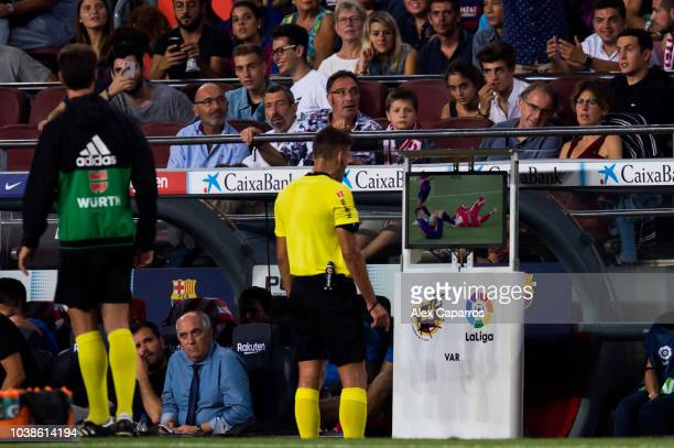 Referee Jesus Gil Manzano looks at the Video Assistant Referee VAR screen before showing a red card to Clement Lenglet of FC Barcelona during the La...