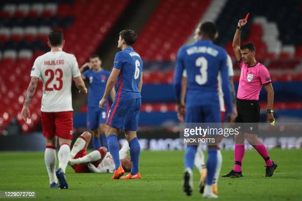 Referee Jesus Gil Manzano shows England's defender Harry Maguire a red card to send him off after getting a second yellow card for a bad challenge...