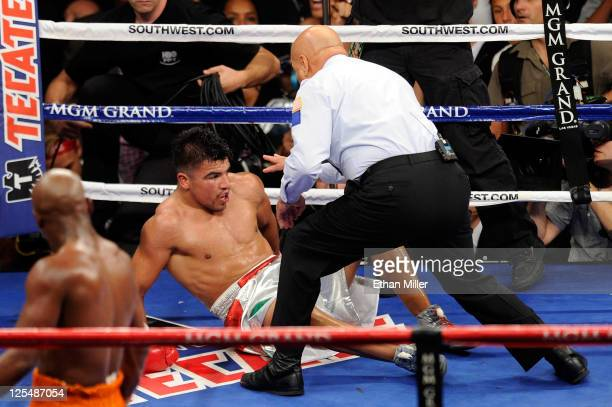 Referee Joe Cortez calls the fight after Victor Ortiz is knocked out by Floyd Mayweather Jr during their WBC welterweight title fight at the MGM...