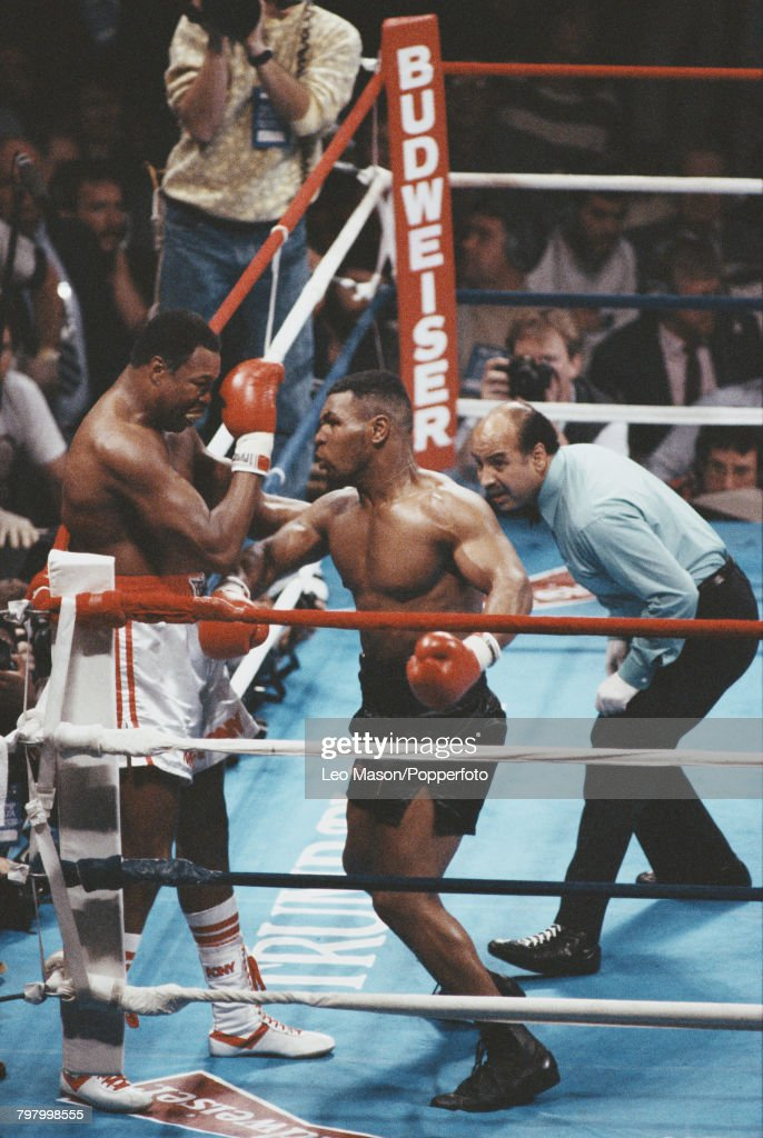 Referee Joe Cortez looks on as American boxer Mike Tyson, pictured right, corners fellow American boxer Larry Holmes on the ropes during action in the fight at the Convention Hall in Atlantic City, New Jersey on 22nd January 1988. Tyson would go on to knock out Holmes in the fourth round to retain his WBA, WBC and IBF heavyweight titles.