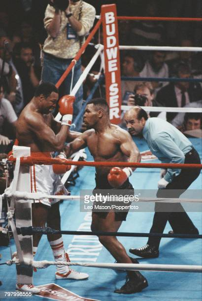 Referee Joe Cortez looks on as American boxer Mike Tyson pictured right corners fellow American boxer Larry Holmes on the ropes during action in the...