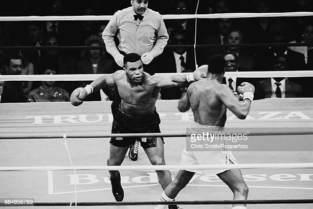 Referee Joe Cortez looks on as American heavyweight boxer Mike Tyson lands a punch to the head of Larry Holmes in their heavyweight title fight at...