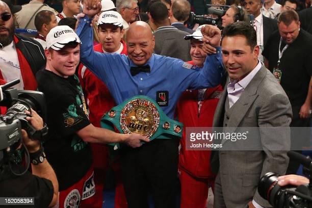 Referee Joe Cortez raises the hands of Canelo Alvarez and promoter Oscar De La Hoya after Alvarez's knockout victory over Josesito Lopez at MGM Grand...