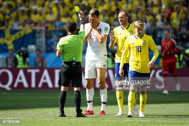 Referee Joel Aguilar of Salvador gives a yellow card to Kim Shinwook of South Korea during the 2018 FIFA World Cup Russia group F match between...
