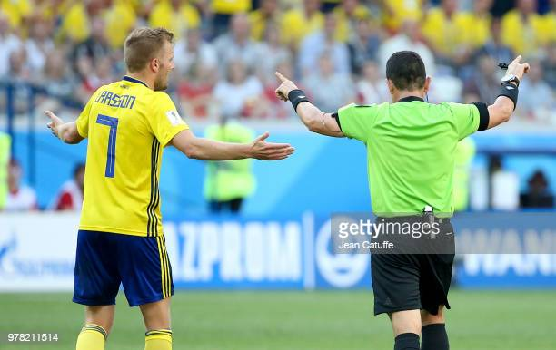 Referee Joel Aguilar of Salvador shows the sign he'll use the video system VAR to allow a penalty for Sweden while Sebastian Larsson of Sweden looks...