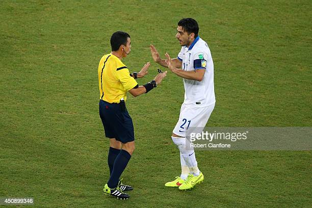 Referee Joel Aguilar speaks to Konstantinos Katsouranis of Greece during the 2014 FIFA World Cup Brazil Group C match between Japan and Greece at...