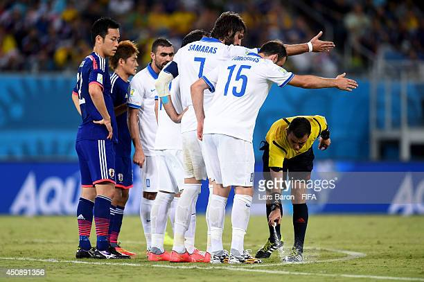 Referee Joel Aguilar sprays the form to draw a line during the 2014 FIFA World Cup Brazil Group C match between Japan and Greece at Estadio das Dunas...