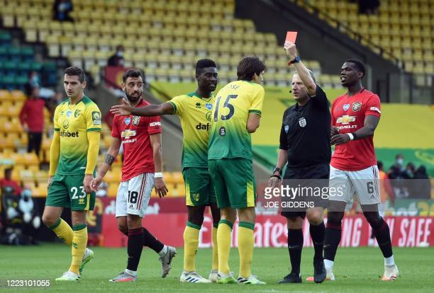 Referee John Moss Norwich City's German-born Swiss defender Timm Klose a red card after a foul on Manchester United's Nigerian striker Odion Ighalo...