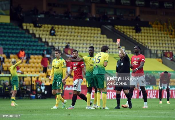 Referee John Moss shows Norwich City's German-born Swiss defender Timm Klose a red card after a foul on Manchester United's Nigerian striker Odion...