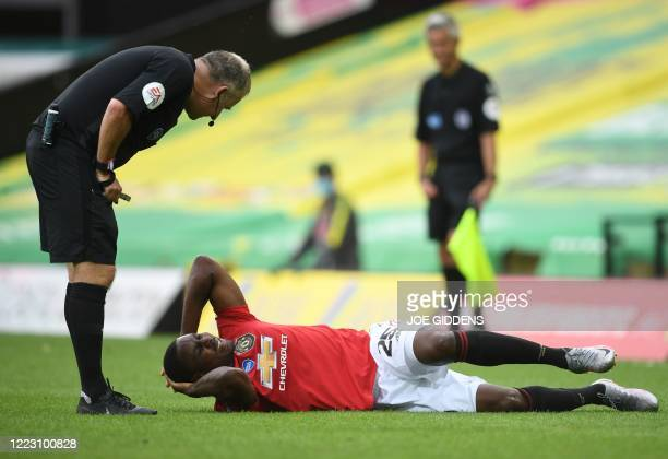 Referee John Moss speaks to Manchester United's Nigerian striker Odion Ighalo during the English FA Cup quarter-final football match between Norwich...