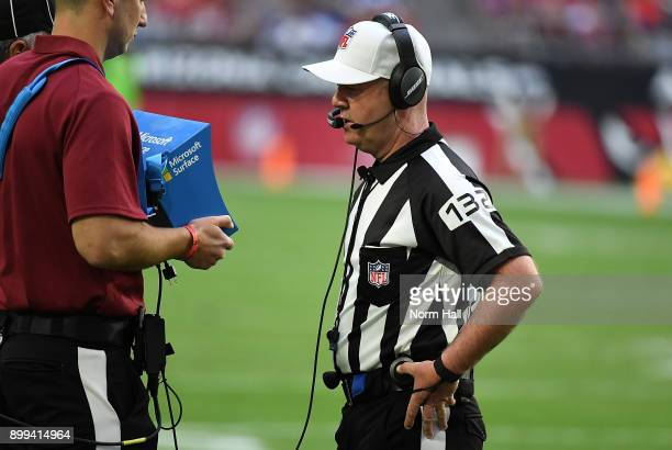NFL referee John Parry watches a replay on a video monitor during a game between the Arizona Cardinals and the New York Giants at University of...