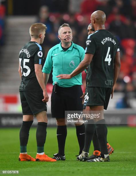 Referee Jon Moss in discussion with Alexander Zinchenko and Vincent Kompany of Manchester City during the Premier League match between Stoke City and...