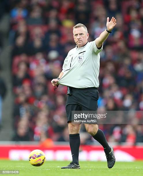 Referee Jon Moss indicates shirt pulling