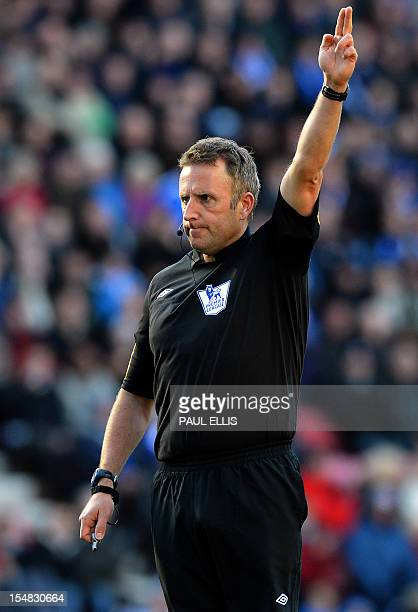 Referee Jon Moss signals during the English Premier League football match between Wigan Athletic and West Ham United at The DW Stadium in Wigan...