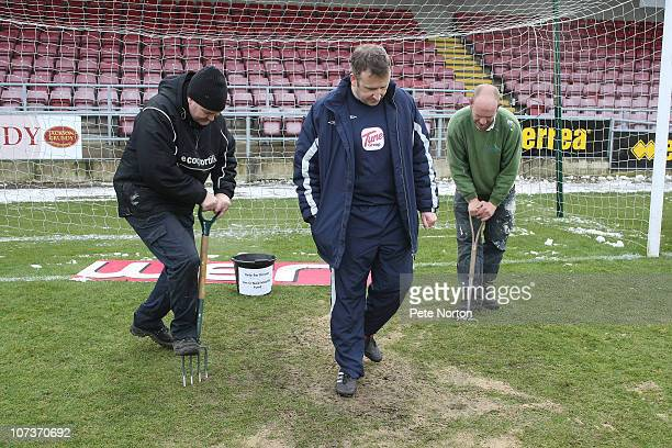 Referee Jon Moss tests a frozen area of the pitch as groundsmen Paul Knowles and Jazon Hawthorn fork the goal mouth during a pitch inspection prior...