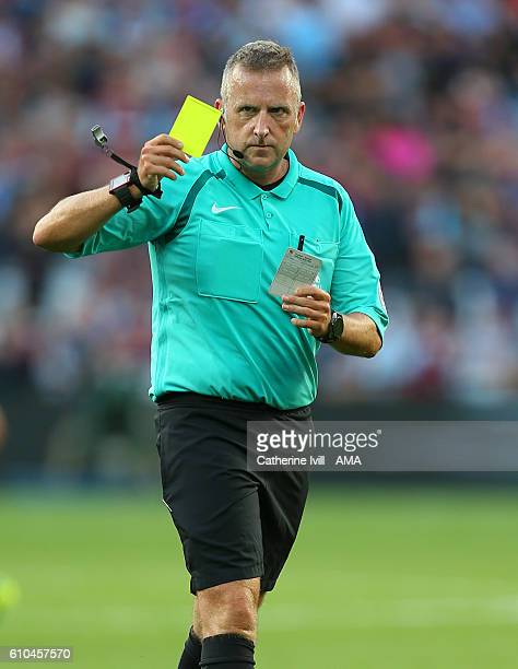 Referee Jon Moss with a yellow card during the Premier League match between West Ham United and Southampton at London Stadium on September 25 2016 in...