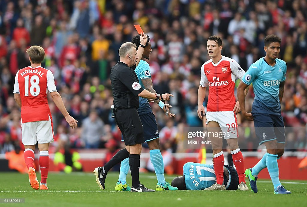 Referee Jonanthan Moss (L) shows Granit Xhaka of Arsenal (R) a red card during the Premier League match between Arsenal and Swansea City at Emirates Stadium on October 15, 2016 in London, England.