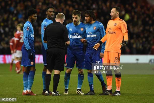 Referee Jonathan Moss and Arsenal players discuss the awarding of the second penalty during the English FA Cup third round football match between...