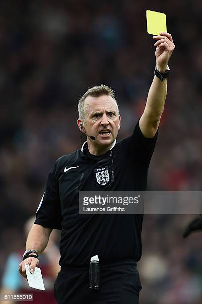 Referee Jonathan Moss shows a yellow card during The Emirates FA Cup fifth round match between Blackburn Rovers and West Ham United at Ewood park on...