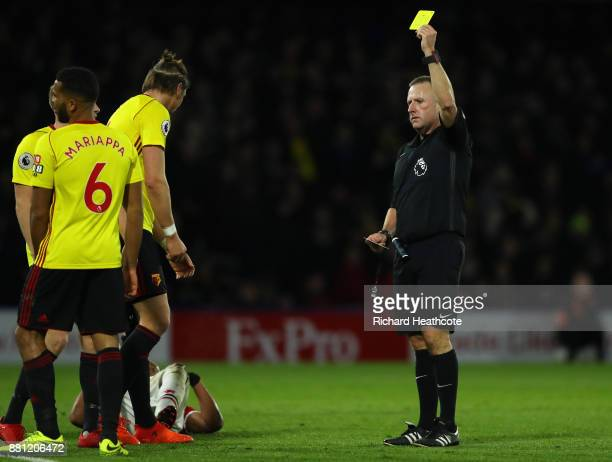 Referee Jonathan Moss shows a yellow card to Adrian Mariappa of Watford during the Premier League match between Watford and Manchester United at...