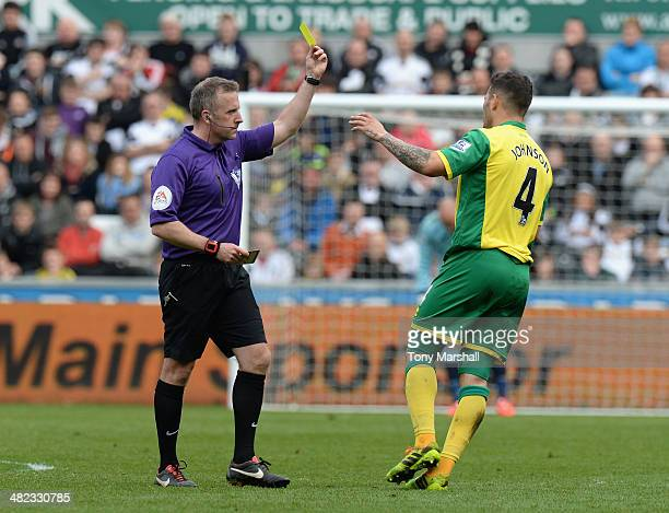 Referee Jonathan Moss shows a yellow card to Bradley Johnson of Norwich City during the Barclays Premier League match between Swansea City and...