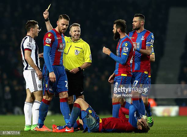 Referee Jonathan Moss shows a yellow card to James Chester of West Bromwich Albion as Yohan Cabaye of Crystal Palace is injured during the Barclays...