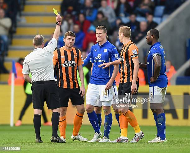 Referee Jonathan Moss shows Alex Bruce of Hull City a yellow card during the Barclays Premier League match between Leicester City and Hull City at...