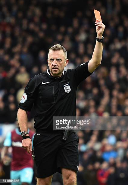 Referee Jonathan Moss shows the red card to Cheikhou Kouyate of West Ham United during The Emirates FA Cup fifth round match between Blackburn Rovers...