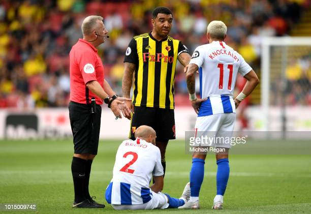 Referee Jonathan Moss speaks with Troy Deeney of Watford and Anthony Knockaert of Brighton and Hove Albion after Bruno Saltor Grau of Brighton and...