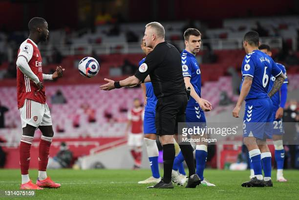 Referee Jonathan Moss takes the ball off Nicolas Pepe of Arsenal after the penalty decision is overturned after a VAR review for offside during the...