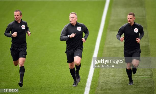Referee Jonathan Moss warms up with his assistants before the English Premier League football match between West Ham United and Arsenal at The London...