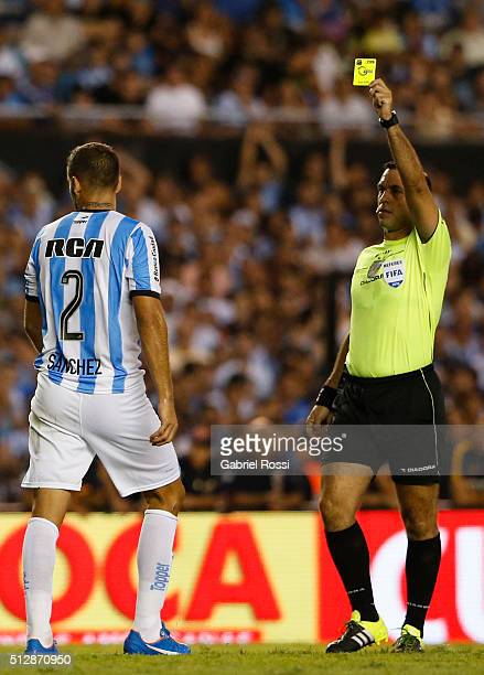 Referee Jorge Baliño shows a yellow card to Nicol‡as S‡anchez of Racing Club during a fifth round match between Racing Club and Boca Juniors as part...