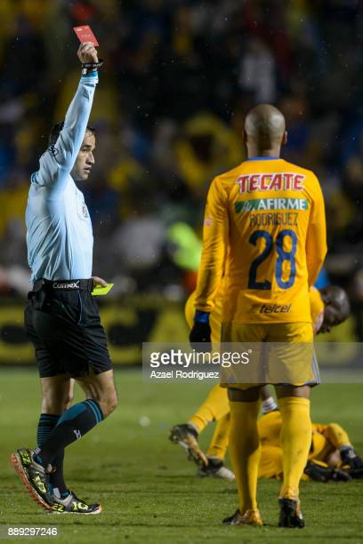 Referee Jorge Isaac Rojas gives a red card to Leonel Vangioni of Monterrey during the first leg of the Torneo Apertura 2017 Liga MX final between...