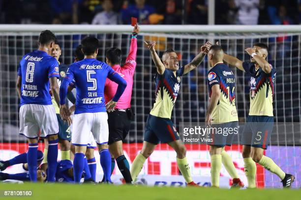 Referee Jorge Isaac Rojas shows the red card to Mateus Uribe of America during the quarter finals first leg match between Cruz Azul and America as...