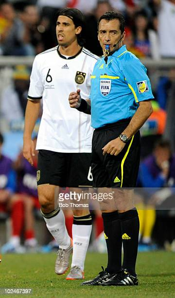 Referee Jorge Larrionda stands near Sami Khedira of Germany during the 2010 FIFA World Cup South Africa Round of Sixteen match between Germany and...