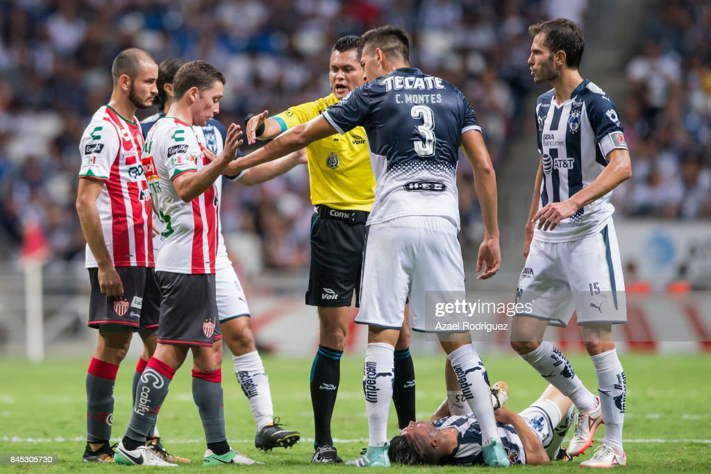 Referee Jorge Perez and Cesar Montes of Monterrey argue with Manuel Iturra of Necaxa during the 8th round match between Monterrey and Necaxa as part of the Torneo Apertura 2017 Liga MX at BBVA Bancomer Stadium on September 9, 2017 in Monterrey, Mexico.