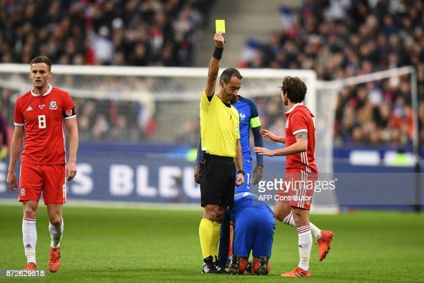 Referee Jorge Sousa gives a yellow card to Wales' midfielder Joe Allen during the friendly football match between France and Wales at the Stade de...