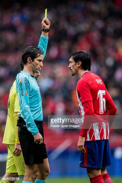 Referee Jose Luis Munuera Montero shows Stefan Savic of Atletico de Madrid the yellow card during the La Liga 201718 match between Atletico de Madrid...