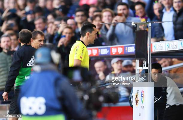 Referee Jose Maria Sanchez Martinez assesses a decision via VAR during the La Liga match between FC Barcelona and Real Madrid CF at Camp Nou on...