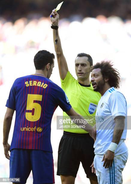 Referee Jose Maria Sanchez Martinez shows a yellow card to Real Madrid's Brazilian defender Marcelo next to Barcelona's Spanish midfielder Sergio...