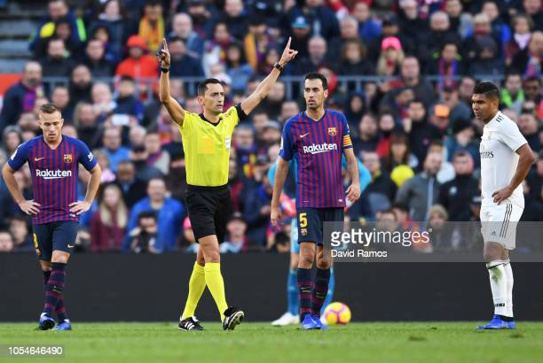 Referee Jose Maria Sanchez Martinez signals for a VAR decision during the La Liga match between FC Barcelona and Real Madrid CF at Camp Nou on...