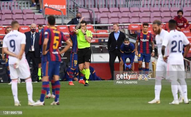 Referee Juan Martinez Munuera awards Real Madrid a penalty following a VAR review during the La Liga Santander match between FC Barcelona and Real...